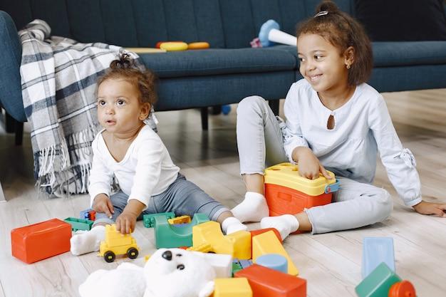 Zwei hübsche kinder sitzen auf dem boden und spielen mit spielzeug in der nähe des sofas. afroamerikanische schwestern, die zu hause spielen.