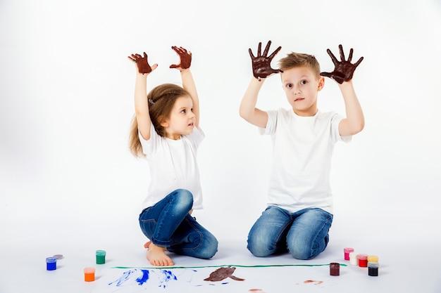 Zwei hübsche kinderfreunde jungen und mädchen zeichnen bilder von farben