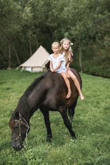 Zwei hübsche kleine blonde mädchen mit langen haaren in freizeitkleidung und boho-accessoires reiten zusammen auf einem braunen pferd