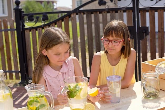 Zwei hübsche kleine mädchen in kleidern bereiten frische kühle limonade zu, während eines von ihnen die hälfte der zitrone in einen glaskrug drückt