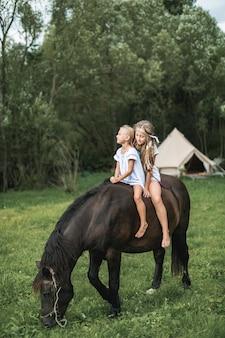 Zwei hübsche kleine mädchen in lässiger boho-kleidung galoppieren auf einem schönen dunklen pferd im freien