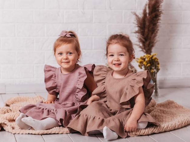 Zwei hübsche kleine mädchen sitzen und lächeln in einem raum auf dem boden
