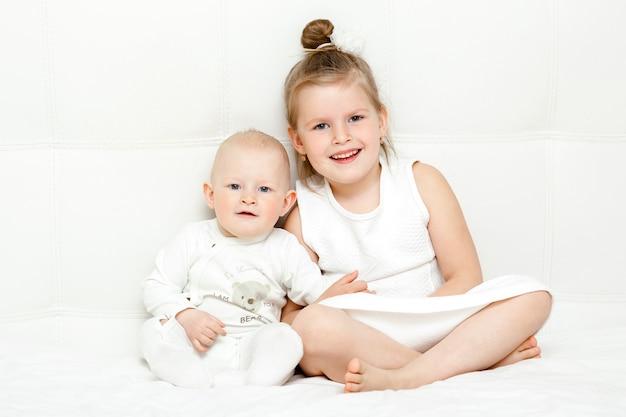 Zwei hübsche kleine schwestern in weißen t-shirts im bett
