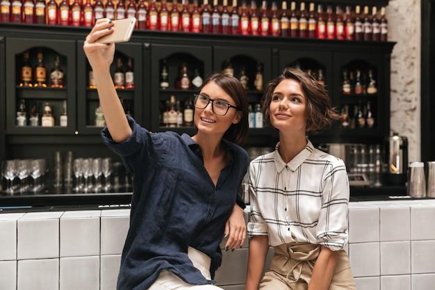 Zwei hübsche lächelnde frauen machen selfie