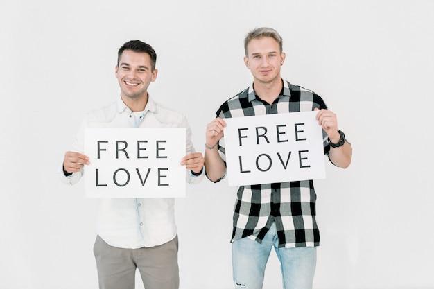 Zwei hübsche lgbt-aktivisten kaukasischer männer, die gegen die diskriminierung von homosexuellen kämpfen, die gleiche liebe frei haben und plakate mit slogans halten