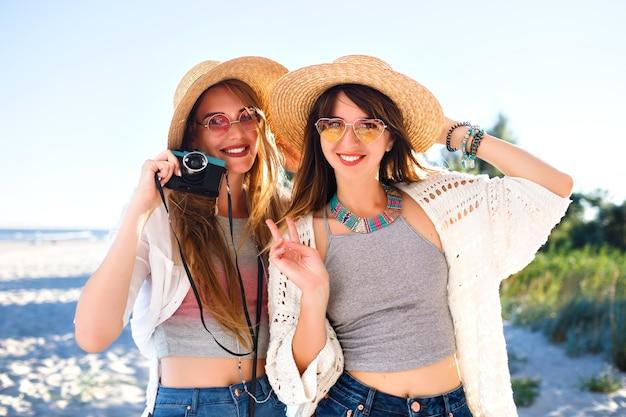 Zwei hübsche lustige schwestermädchen machen selfie auf vintage-kamera, posieren am strand, party- und urlaubsstimmung, verrücktes positives gefühl, sommerhelle kleidung, sonnenbrille und hüte.