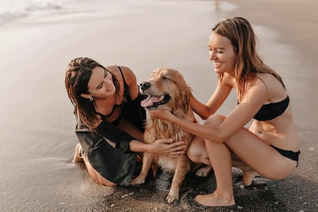 Zwei hübsche mädchen am strand nahe dem ozean, der mit einem hund auf sonnenuntergang spielt