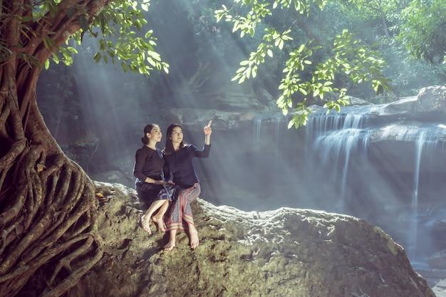 Zwei hübsche mädchen, die nahe dem wasserfall sich entspannen.