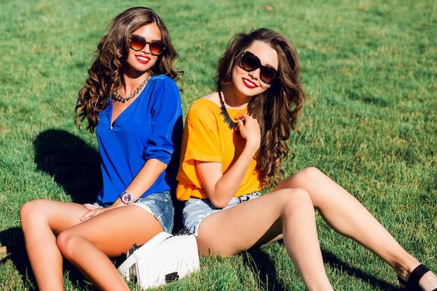 Zwei hübsche mädchen in hellen sommerkleidern, die auf gras aufwerfen und sonnigen tag zusammen genießen