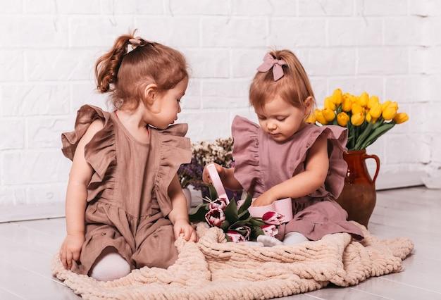 Zwei hübsche mädchen in schönen kleidern öffnen eine schachtel mit einem geschenk in einem raum mit blumen