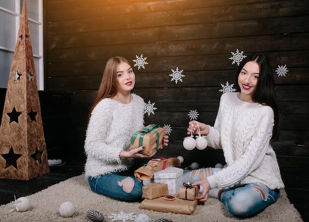 Zwei hübsche mädchen mit geschenken für weihnachten