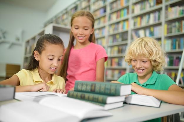 Zwei hübsche mädchen und ein netter junge mit blonden welligen haaren lesen bücher am schreibtisch