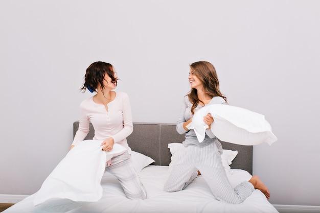 Zwei hübsche pyjamamädchen, die kissenschlacht auf bett haben. sie lachen miteinander.