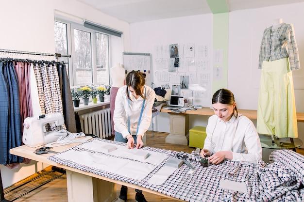 Zwei hübsche schneiderinnen, die im modeatelier mit stilvollem stoff arbeiten, auf dem sie das muster mit schneiderkreide markiert haben. karierter stoff, zentimeterband, schneiderschere