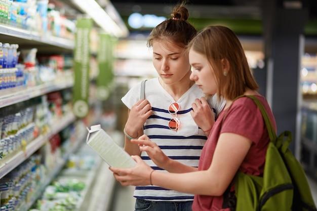 Zwei hübsche schwestern gehen zusammen einkaufen, stehen im lebensmittelgeschäft, wählen frische milch in papierbehältern aus, lesen etikett, tragen rucksäcke, haben ernsthafte gesichtsausdrücke. menschen- und handelskonzept