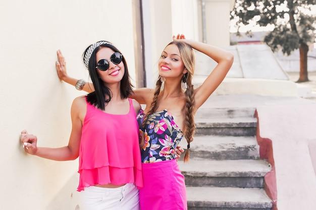 Zwei hübsche schwestern hipster mädchen umarmen sich und haben spaß zusammen