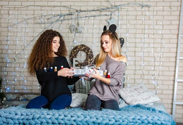 Zwei hübsche schwestern in weihnachtspullovern knien auf einem gestrickten plaid und halten ein neujahrsgeschenk mit den händen zusammen