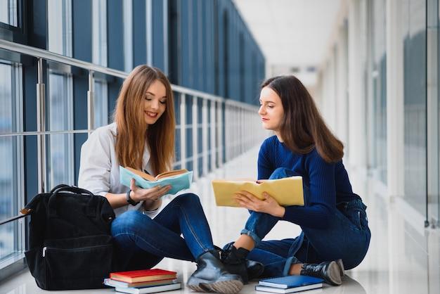 Zwei hübsche studentinnen mit büchern, die auf dem boden im flur der universität sitzen
