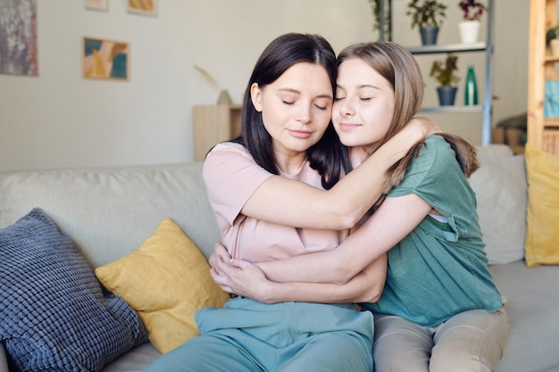 Zwei hübsche und liebevolle frauen in freizeitkleidung, die sich nach der versöhnung umarmen, während sie auf der couch in der häuslichen umgebung sitzen