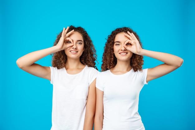 Zwei hübsche zwillingsmädchen lächelnd und scherzen über blaue wand