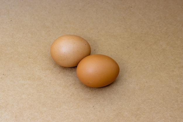 Zwei hühnereier isoliert auf kokosnussholzoberfläche