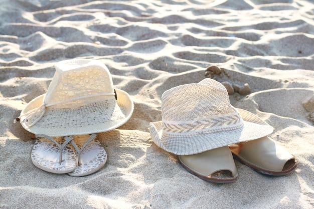 Zwei hüte und sandalen liegen auf sand