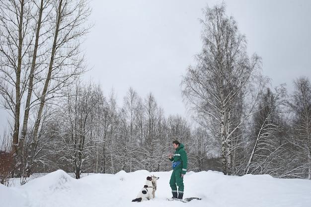 Zwei hunde laufen im winter mit einem besitzer im freien