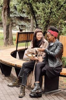 Zwei hungrige freundinnen mit snacks und getränken im park