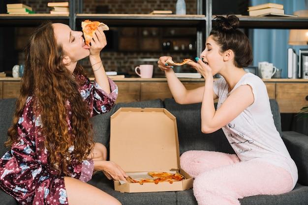 Zwei hungrige junge frauen, die pizza essen