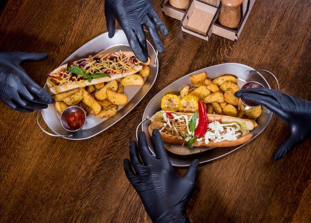 Zwei hungrige junge männer, die einen hot dog im café essen. restaurant