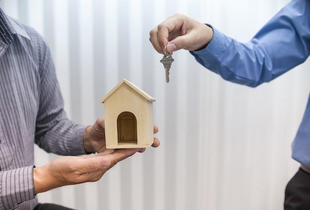 Zwei immobilienmakler halten schlüssel und hausmodelle