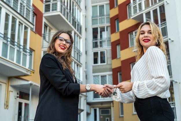 Zwei immobilienmakler zeigen haus zum verkauf oder zur miete