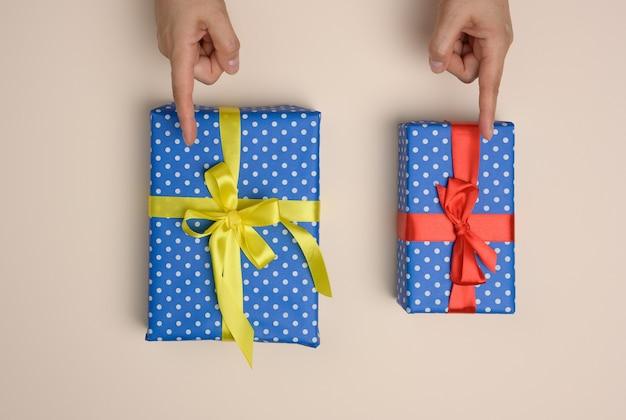 Zwei in seidenband gewickelte geschenkboxen auf beigem hintergrund, weibliche finger zeigen die wahl an