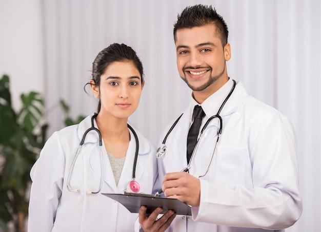 Zwei indische doktoren, die zusammenarbeiten sitzen.