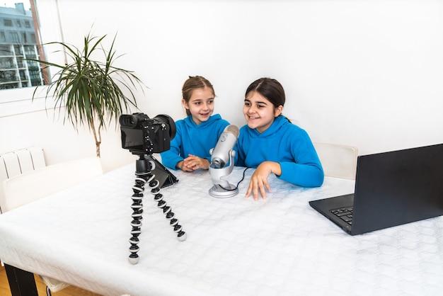 Zwei influencer-schwestern und blogger, die live aus ihrem wohnzimmer übertragen, lachen und in die kamera schauen und auf einer video- oder sozialen netzwerkplattform in das mikrofon sprechen