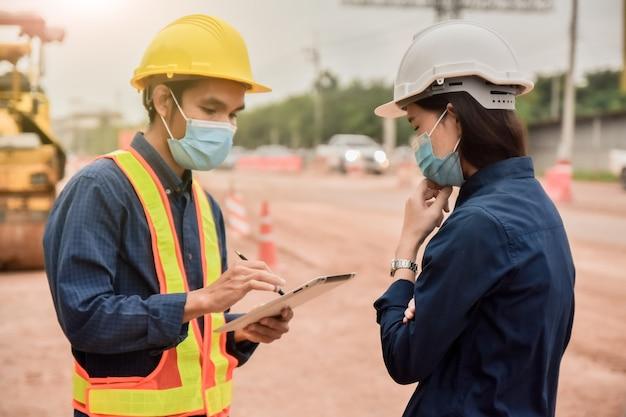 Zwei ingenieur, der tablette hält, die auf baustellenkonstruktion spricht