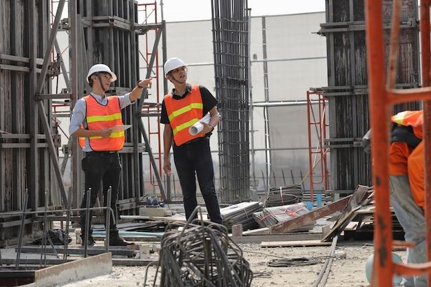 Zwei ingenieure arbeiten auf der baustelle. sie überprüfen den fortschritt der arbeit.