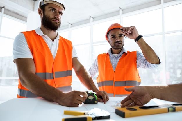 Zwei ingenieure betrachten den projektplan auf dem tisch auf der baustelle