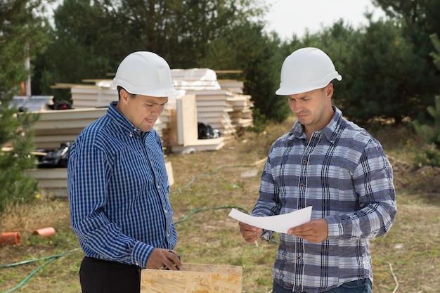 Zwei ingenieure diskutieren vor ort, während sie ein dokument diskutieren, hinter dem stapel von isolierten holzplatten im blick sind