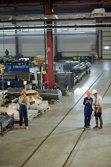 Zwei ingenieure in arbeitskleidung diskutieren präsentationspunkte auf tablets, während ihr kollege eine riesige industriemaschine steuert