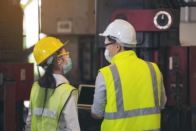 Zwei ingenieure in schutzhelm tragen sicherheit mit laptop für die planung eines projekts.