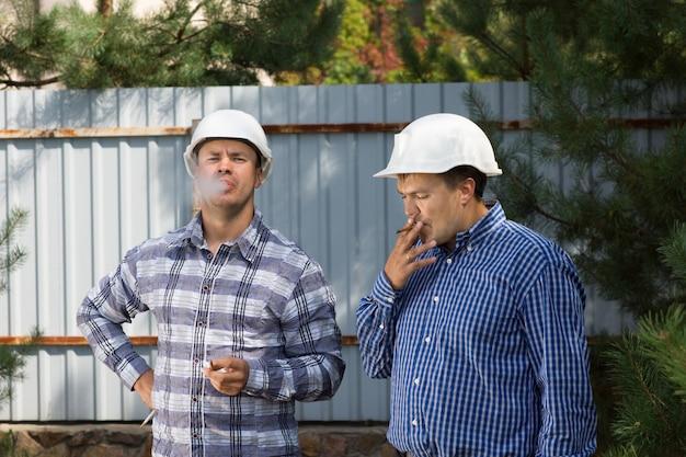 Zwei ingenieure machen eine rauchpause in ihren helmen und stehen im schatten eines baumes auf einer baustelle und paffen an ihren zigaretten cigarette