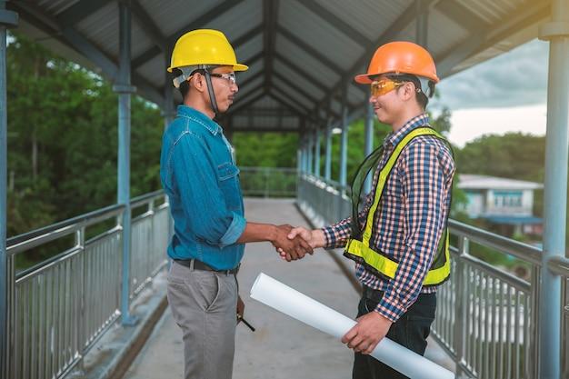 Zwei ingenieure stehen hand in hand auf der brücke