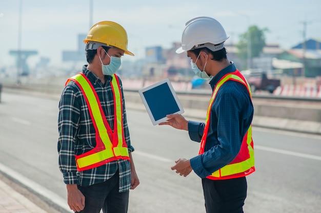 Zwei ingenieure tragen gesichtsmaske mit tablet-arbeit im freien vor ort umfrage