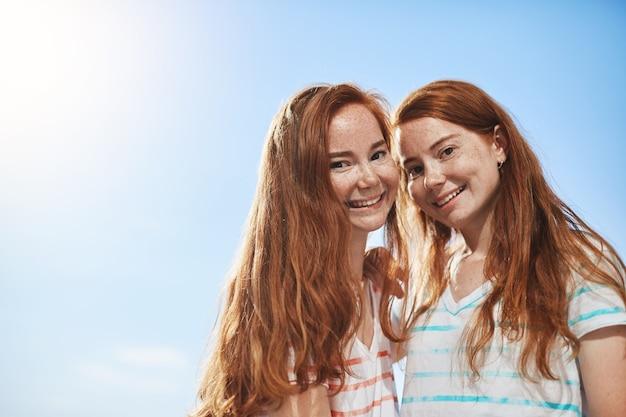 Zwei ingwermädchen, die an einem sonnigen sommertag lächeln. eine zwillingsschwester zu haben ist ein großes glück.