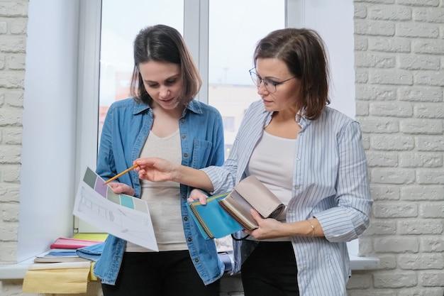 Zwei innenarchitektinnen und kunden, die stoffe für heimtextilien, vorhänge und möbelpolster auswählen