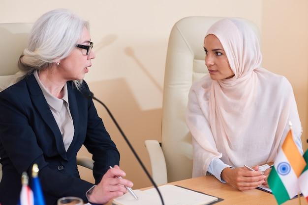 Zwei interkulturelle delegierte diskutieren punkte ihrer kollegiumsrede am tisch und bereiten fragen vor