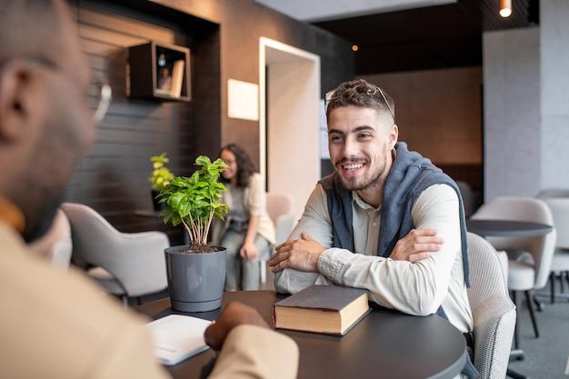 Zwei interkulturelle studenten diskutieren am tisch im café