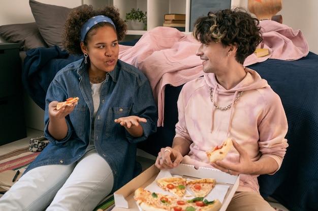 Zwei interkulturelle teenager diskutieren etwas beim pizzaessen