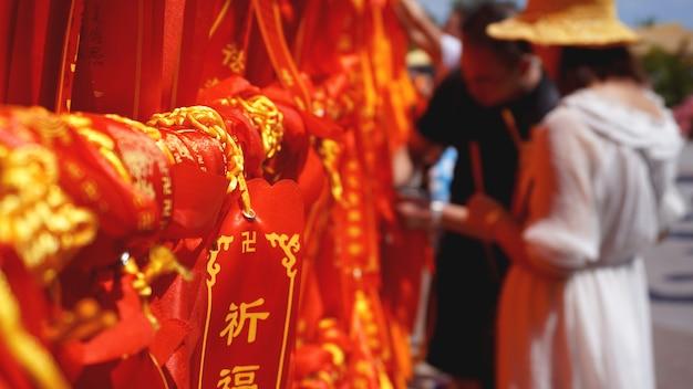 Zwei internationale touristen suchen und lesen mehrere bänder mit wünschen. touristen banden eine rote schleife, china